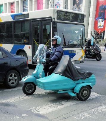 A lovely lady with a turquoise vespa with a sidecar