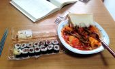 Greek traditional food with green beans and tomato sauce (fasolakia) accompanied by salmon maki sushi